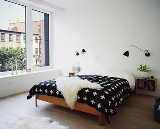 Our Scandinavian Style Dreams Come True in This Brooklyn Town House - Photo 6 of 9 - Set atop a BoConcept bed, a graphic blanket by Pia Wallén for HAY punctuates the master bedroom. The sconces are by Robert Dudley Best for Bestlite.