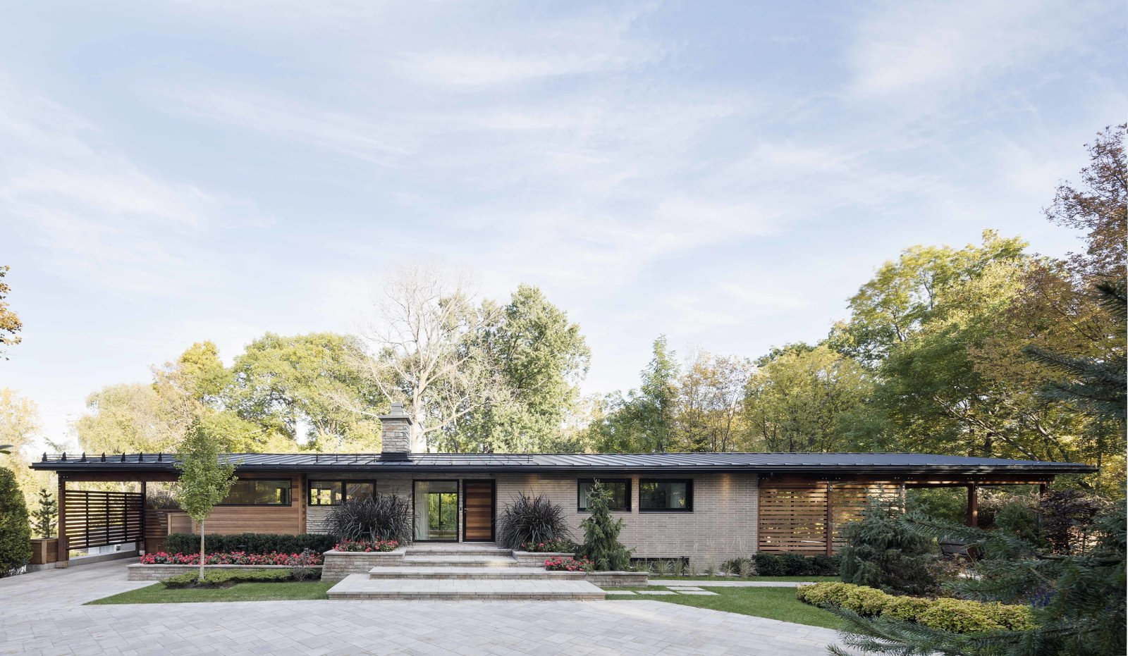 The horizontal layout of the home allows for easy movement throughout the interior, while the line of the continuous roof seems to extend into the trees. Enlarging the opening of the home allowed for impressive views of the river and surrounding area.
