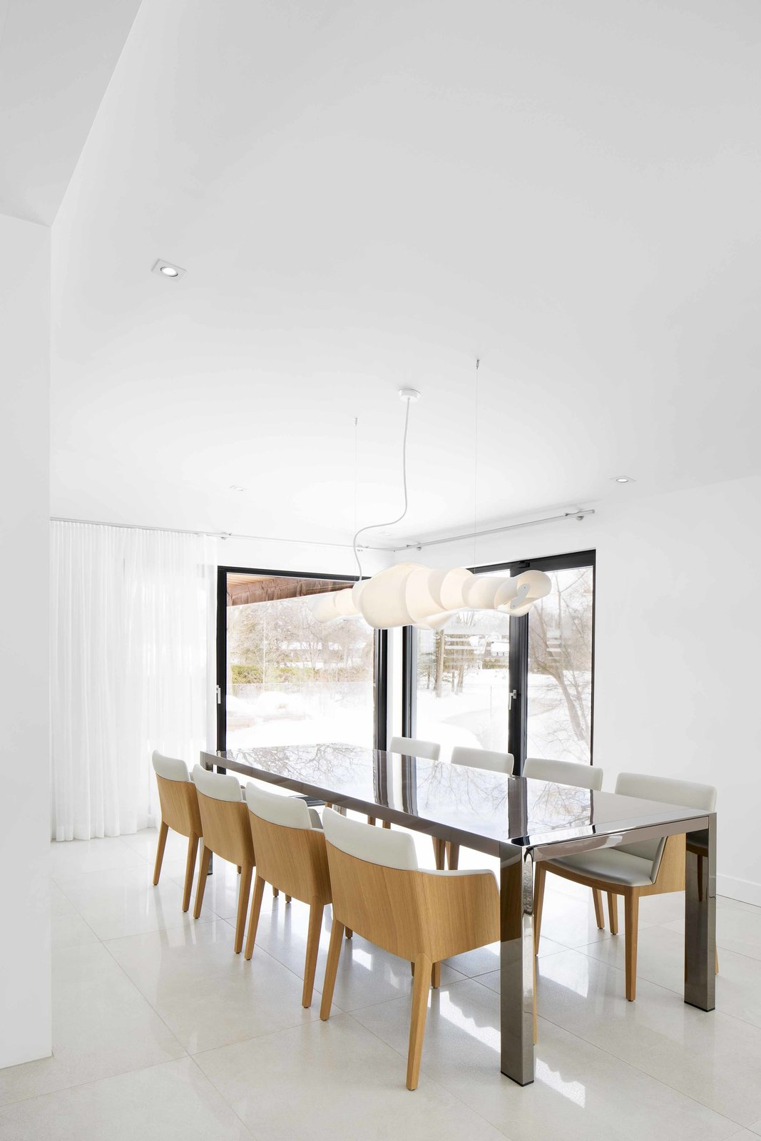 Playful stylistic details, such as two-toned dining chairs from Latitude Nord and a creative lighting fixture from Au Courant, are juxtaposed with the rest of the home's tranquil elegance.  Photo 10 of 12 in How to Refresh a Midcentury Gem in Quebec? Winter-White Everything