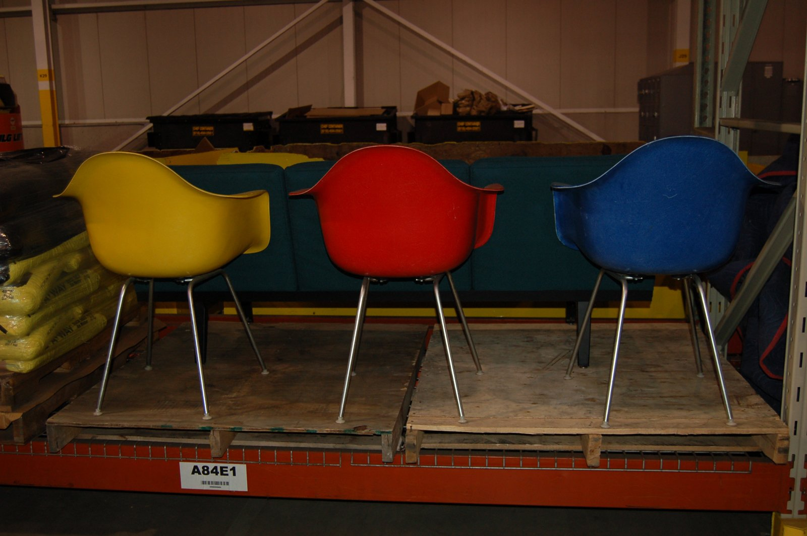 "We headed over to a big warehouse space to look for hidden gems. Here we see a trio of vintage Eames Plastic Arm Chairs, which were first produced in 1950. The Eames first introduced the chair in 1948 as their concept for the Museum of Modern Art's ""International Competition for Low-Cost Furniture"". Originally conceived in stamped metal for the contest, the Eames and Herman Miller began exploring fiberglass as an ever lower-cost material option. The piece, which has gone through many iterations, was the first mass-produced plastic chair.  Inside the Herman Miller Headquarters by Amanda Dameron"