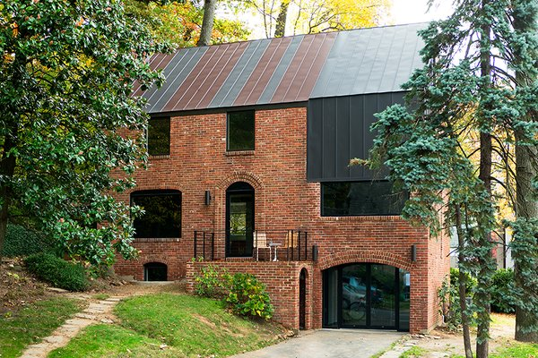 Steel Preserve - Photo 1 of 5 - In Arlington, Virginia, a drafty house was made more than twice as efficient with the addition of metal both inside and out. Roof panels topping the brick envelope echo its original geometry.