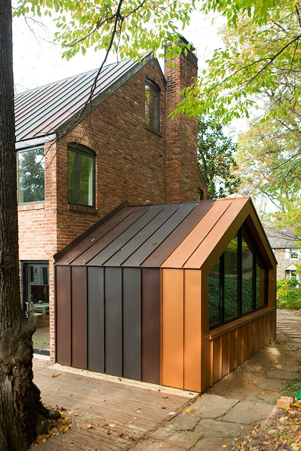 The den, originally and enclosed porch off the back of the house, was one of the biggest energy-sucking culprits. The designers opened it to the rest of the house to improve circulation, added a pentagonal Weather Shiel window, and clad the structure in metal panels matching the roof. Tagged: Exterior, Metal Roof Material, Metal Siding Material, Brick Siding Material, and House.  Photo 3 of 5 in Steel Preserve