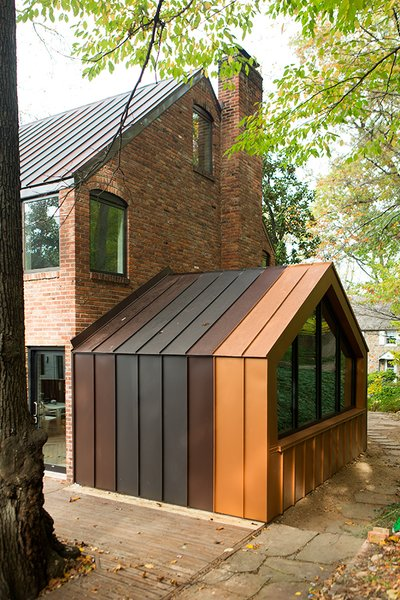 The den, originally and enclosed porch off the back of the house, was one of the biggest energy-sucking culprits. The designers opened it to the rest of the house to improve circulation, added a pentagonal Weather Shiel window, and clad the structure in metal panels matching the roof.