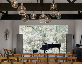 Wouldn't You Like to Have Your Own Private Concerts at Home? - Photo 8 of 10 - Located in the renovated barn, the living room can be transformed into a performance space that seats 80. The art piece is from South Africa. Accompanying the Steinway piano is a sideboard from Restoration Hardware; the pendants are from Cisco Home.