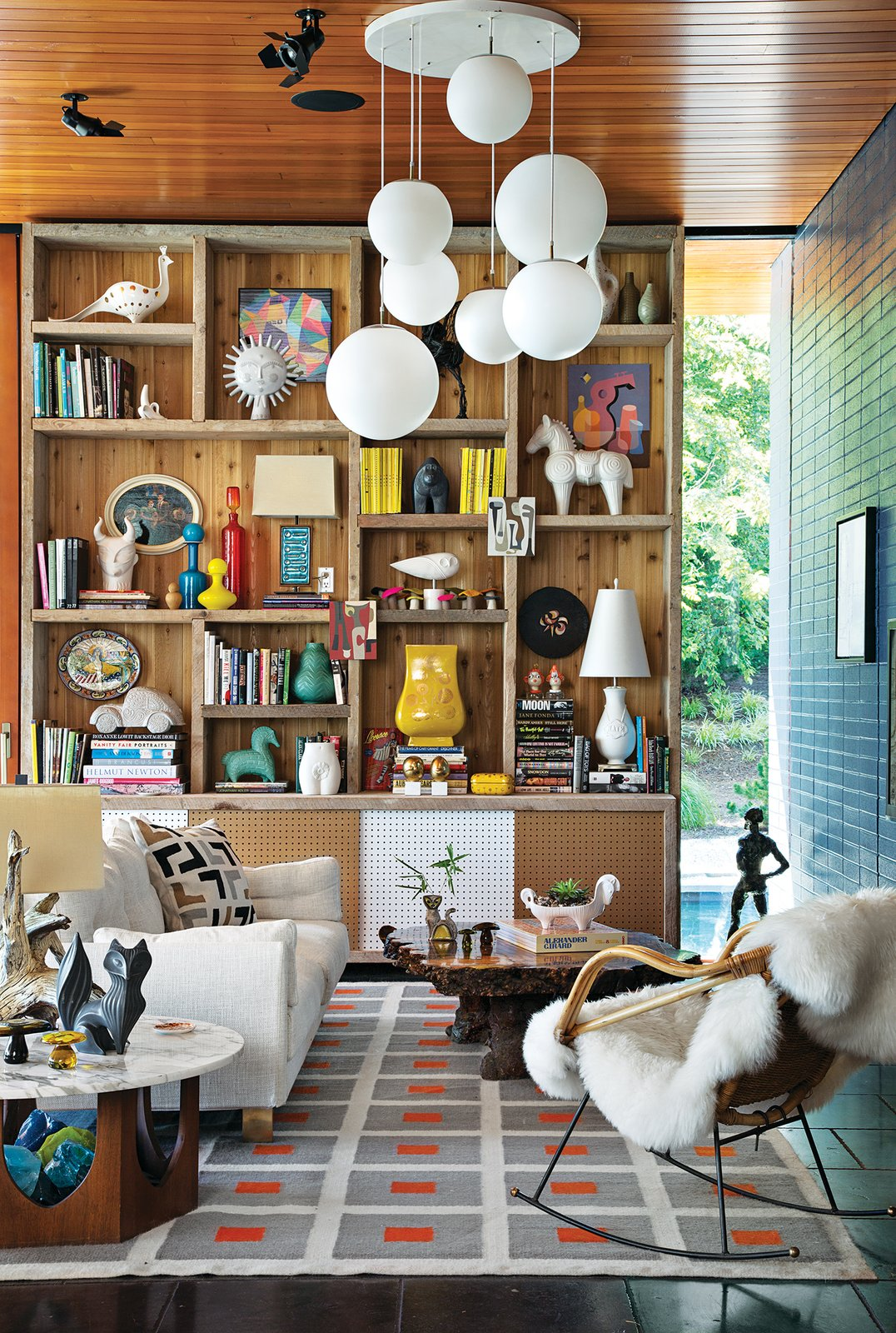 The site-sensitive exterior belies an interior festooned with a kaleidoscopic mix of colors and an array of tactile materials. The Peter rug, Malibu sofa, and ceramics are Adler's own designs. The tables, pendant lights, and rocker are vintage. Adler and Doonan used scaffolding from the house's construction to build the bookshelf.  127+ Inspiring Interior Ideas by Dwell from Jonathan Adler and Simon Doonan Go Trippy Contemporary on Shelter Island