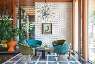 "Jonathan Adler and Simon Doonan Go Trippy Contemporary on Shelter Island - Photo 3 of 12 - ""There's no right answer except to play and experiment,"" Adler says about furnishing the interior. He reupholstered vintage Warren Platner chairs with velvet from Kravet. Drawings by Eva Hesse inspired the custom ceramic wall tile. Adler also created the coffee table, rug, planters, and gold stool. The pendant lamp is from Rewire in Los Angeles and the artwork is by Jean-Pierre Clement."