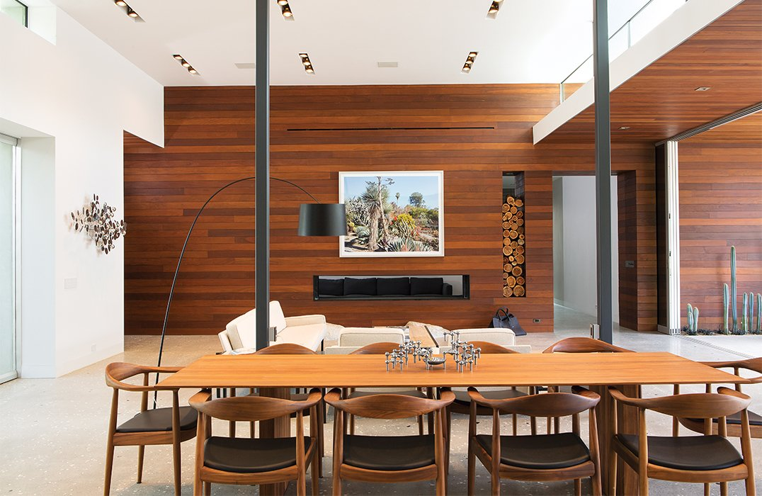 Ipe paneling and concrete floors continue into the living area, where a photograph by Scott McFarland hangs above the fireplace. Surrounding the dining table, by Riva 1920, are walnut chairs the couple found locally. Tagged: Dining Room, Table, and Chair.  Photo 6 of 13 in One Canadian Family Beats the Cold by Escaping to Palm Springs