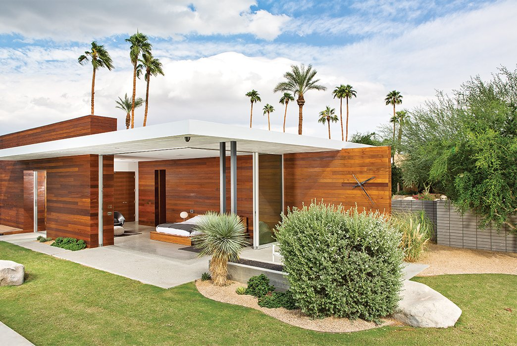 The master bedroom opens on two sides to the outdoors, where Lockyer placed a custom black-chrome wall clock.  Photo 10 of 13 in One Canadian Family Beats the Cold by Escaping to Palm Springs