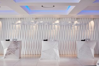 This Revived Greek Resort Will Soon Be at the Top of Your List - Photo 9 of 11 - When you proceed to check in, you'll see that Mahmoud had large blocks of solid Thassos marble carved into sharp geometric shapes to contrast against the more classic, softer lines—each one weighs over five tons. The sculpted wall is inspired by the marble draperies of the antique statues of Delos.