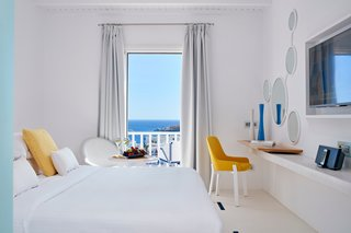 This Revived Greek Resort Will Soon Be at the Top of Your List - Photo 7 of 11 - In the Seabreeze Room, marble floors and floating shelves repeat the use of this local material. Custom Flos lighting designs allow the space to softly glow, while a private balcony looks out to the rest of the coastal property.