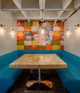 This Retro Apartment Is Finally the Good Kind of Funky - Photo 3 of 7 - The studio created a breakfast nook with a colorful mural in the heart of the home. The metal sconces are custom.