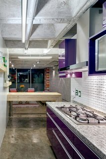 This Retro Apartment Is Finally the Good Kind of Funky - Photo 4 of 7 - Synthetic, organic, and industrial materials coexist in the kitchen. The cabinets are finished in aubergine-purple polyester, the breakfast bench is made of an upcycled timber beam, and the range hood is steel.