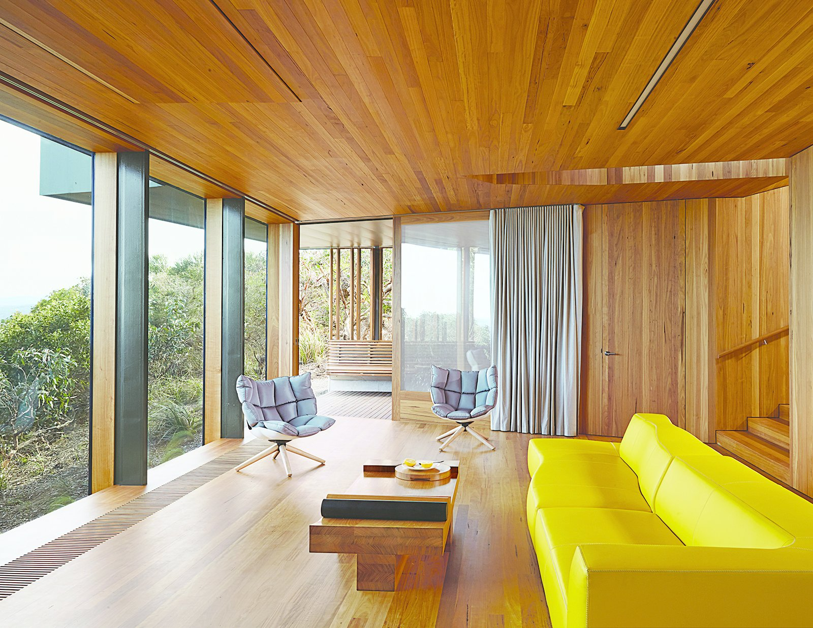 Refusing to fixate on the seascape at the expense of other views, Wardle oriented the living room to a lush grove of trees. A yellow Bend sofa and two Husk chairs, both by Patricia Urquiola for B&B Italia, add splashes of color.  Photo 4 of 10 in This Surfer Rules the Ocean from a Cliffside House
