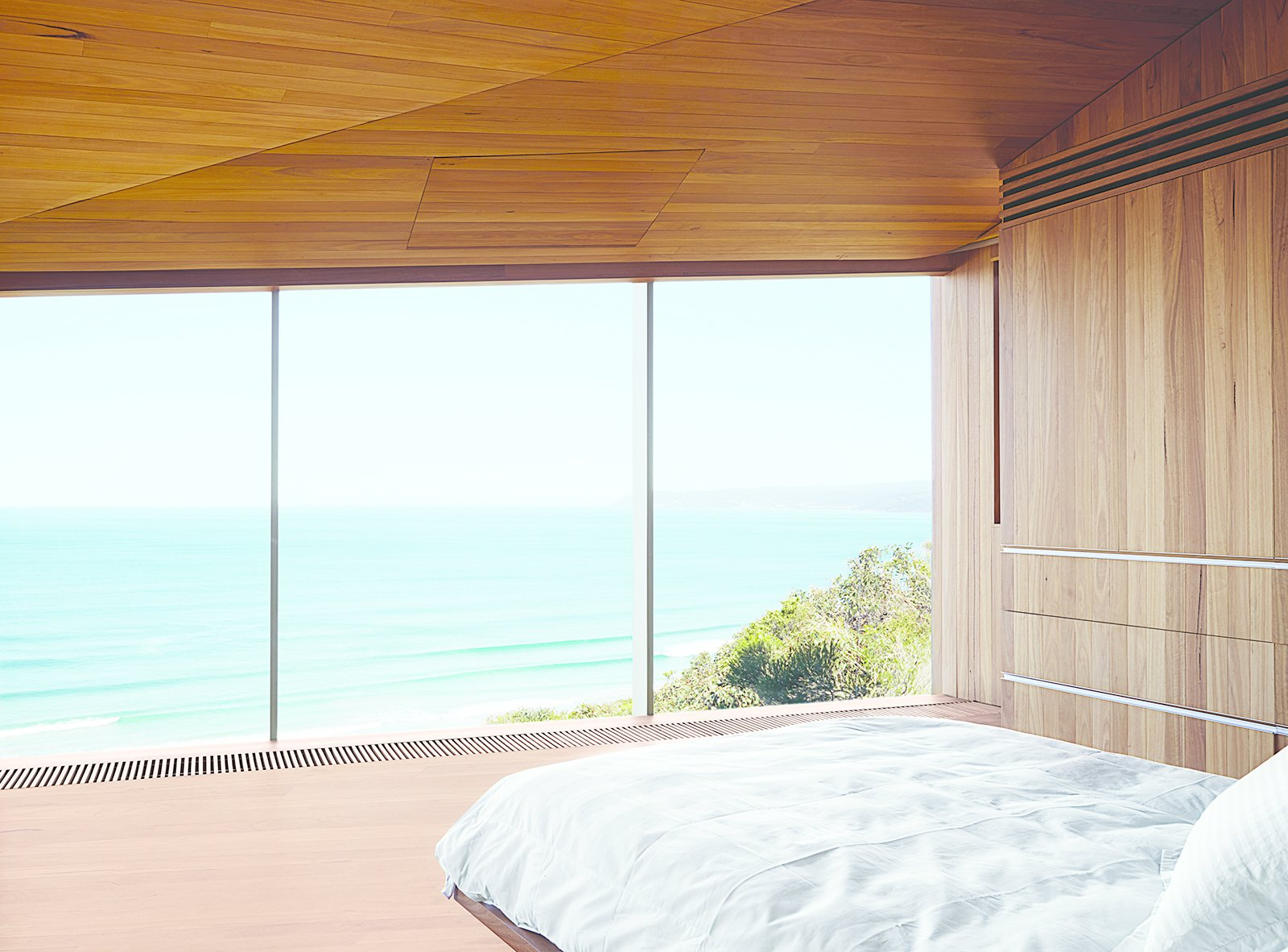 The couple, both surfers and beach lovers, wake up to stunning views of the azure-blue Southern Ocean in their otherwise monochromatic eucalyptus master bedroom. Wardle's firm designed the bed base, and the panel in the ceiling hides a television.  Views by DAVE MORIN from This Surfer Rules the Ocean from a Cliffside House