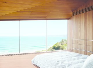 This Surfer Rules the Ocean from a Cliffside House - Photo 7 of 9 - The couple, both surfers and beach lovers, wake up to stunning views of the azure-blue Southern Ocean in their otherwise monochromatic eucalyptus master bedroom. Wardle's firm designed the bed base, and the panel in the ceiling hides a television.
