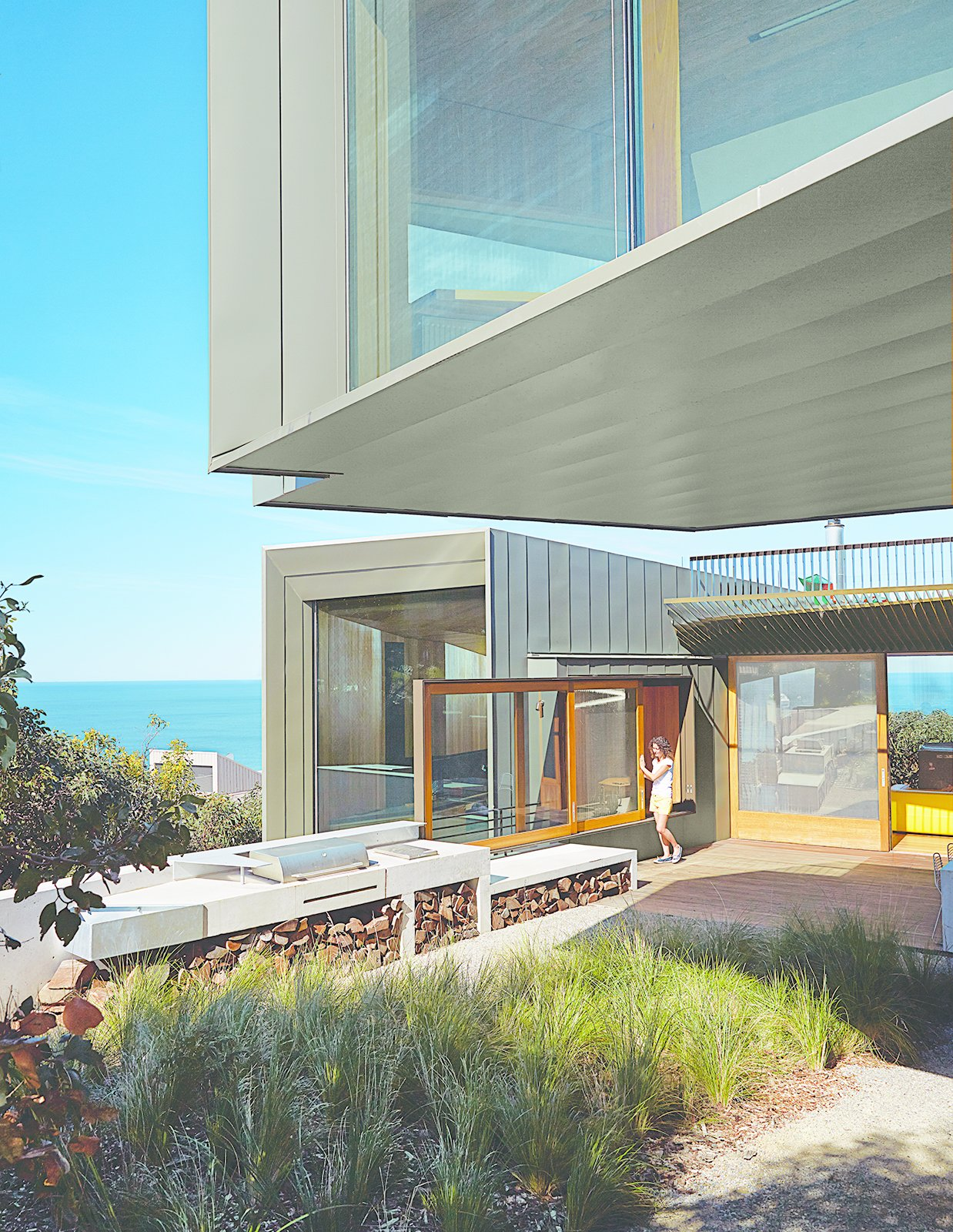 A sliding windows between the kitchen and the barbecue area makes outdoor cooking a cinch.  Photo 9 of 10 in This Surfer Rules the Ocean from a Cliffside House