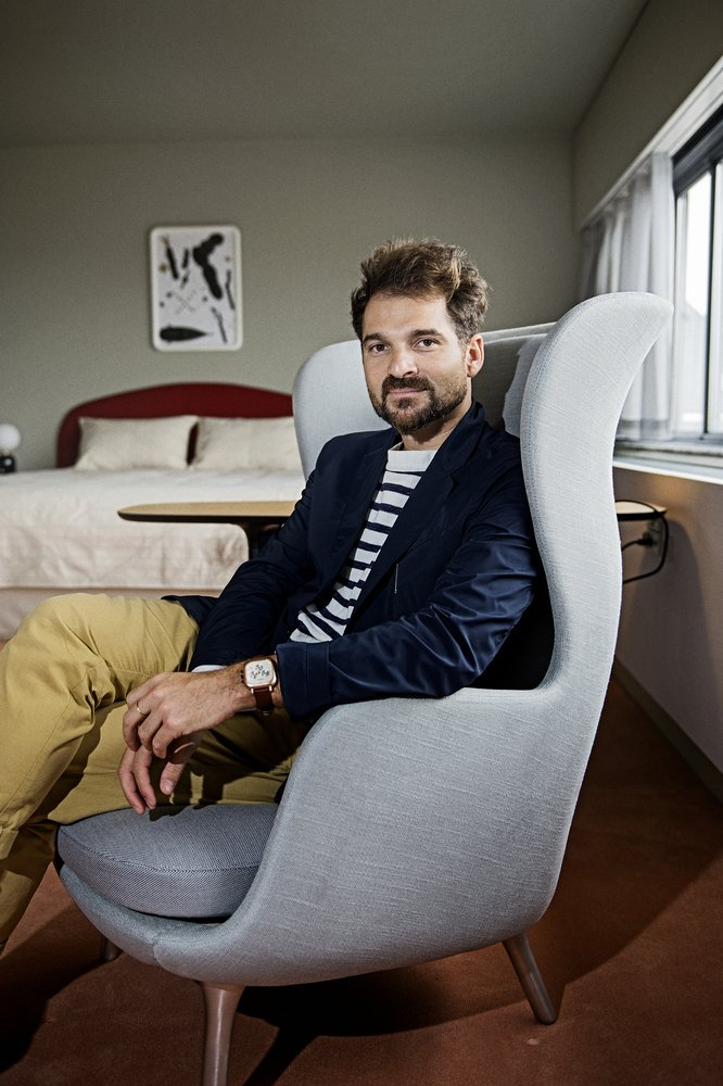Hayon sits in the Ro armchair he designed for Fritz Hansen, one of the items he placed in the room.