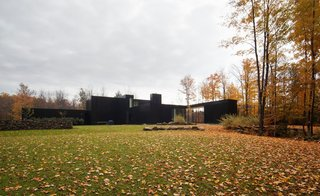 This Family Never Has to Fight About Where Their Next Trip Will Be - Photo 1 of 4 - The black-lacquered aluminum panels and double-height volumes of this home in southern Quebec, designed by Les Architectes FABG, abstract its scale from the outside.