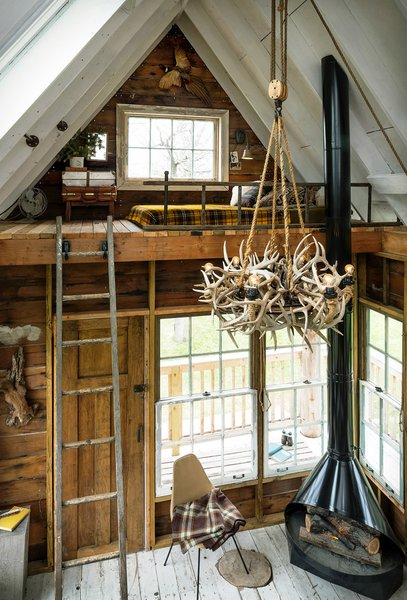 The interior of a treehouse at the camp features a wood-burning stove and antler chandelier.