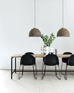 Morten Bo Jensen, of Danish industrial design company Vipp, and his partner, graphic designer Kristina May Olsen, have mixed repurposed vintage items with their own creations inside their Copenhagen apartment. In the kitchen, the dining table—Jensen's first piece for Vipp—is made of powder-coated aluminum frame with a recycled, untreated teak top. The lamps overheard are salvaged and rewired Copenhagen streetlights.