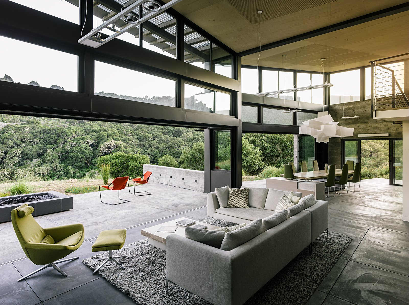 In the open living-dining area, a sofa by Antonio Citterio joins a Metropolitan chair and ottoman, all from B&B Italia. A Big Bang fixture from Foscarini hangs above the dining room table, designed by Feldman and surrounded by chairs from Ligne Roset.  Photo 7 of 11 in Retirement Never Looked Better and More Sustainable