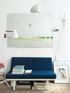 Enter the Parisian Flat of a Globetrotting Artistic Director - Photo 9 of 12 - Aumas outfitted a vintage steel-frame sofa by George Nelson in navy blue fabric from Kvadrat and hung one of his own photos just above it. The lamp to the left of the sofa is a 1960s design found at a Lisbon flea market, and to the right of the sofa is a Two-Arms rotating sconce by the mid-century French designer Serge Mouille.
