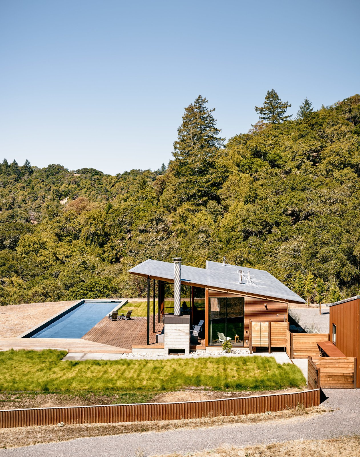 A tradition of weekend hiking trips served as the premise for Jeff and Millie Baird's off-the-grid retreat in California's Sonoma County. Affectionately named Camp Baird, the home is located on a 165-acre parcel near a campsite the couple and their two young daughters had visited for years. Architect Malcolm Davis worked with contractors Fairweather & Associates on the new build; landscape architect Cary Bush of Merge Studio incorporated drought-resistant nativeplantings into the property. Tagged: Large Pools, Tubs, Shower, Wood Patio, Porch, Deck, Large Patio, Porch, Deck, Swimming Pools, Tubs, Shower, Grass, Metal Fences, Wall, Exterior, House, Metal Roof Material, Metal Siding Material, Wood Siding Material, and Cabin Building Type.  Off the grid by Michela O'Connor Abrams from Goodbye Grid and Cushy Beds, Hello Pool in the Wilderness
