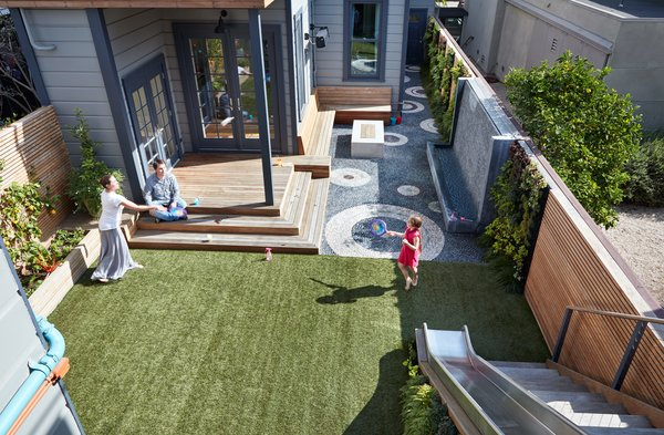 A pebble mosaic and artificial turf divide the yard into zones that never need to be mowed.