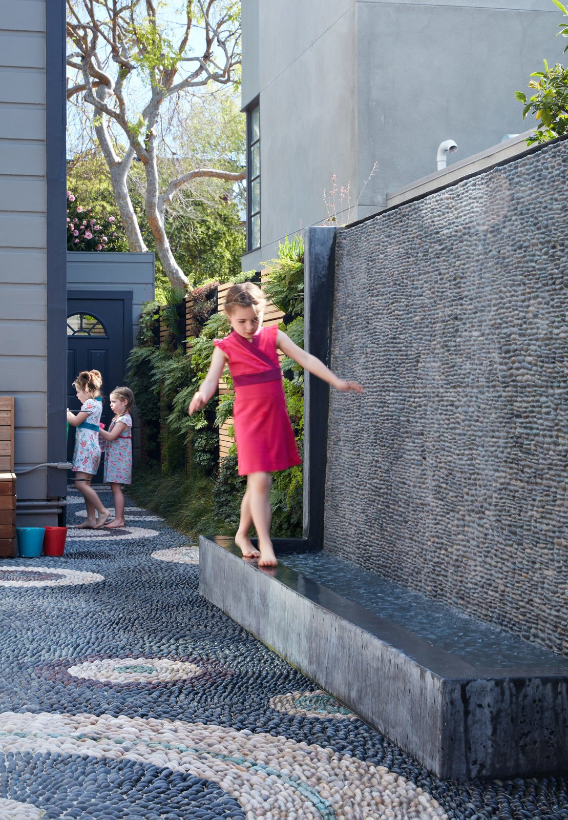The water wall was one of the family's main requests. Not only does it provide the girls— Serafina, Carolina, and Madeleine—a place to play, it also blocks street noise.  Photo 5 of 6 in A Heavenly Backyard is Precise with Pebbles