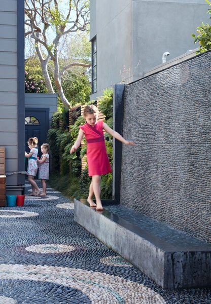 The water wall was one of the family's main requests. Not only does it provide the girls— Serafina, Carolina, and Madeleine—a place to play, it also blocks street noise.