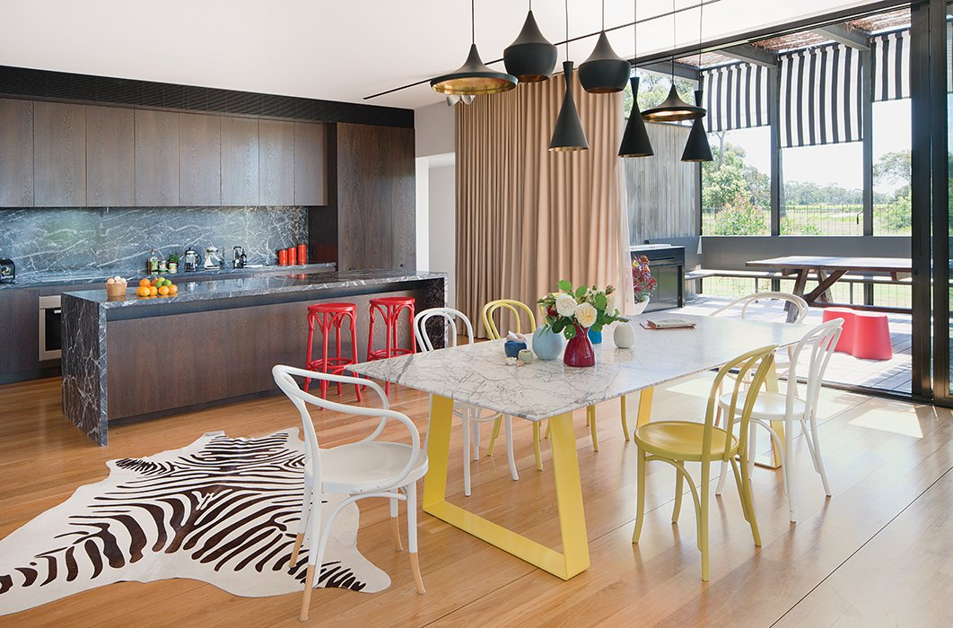 "Tom Dixon pendant lamps hang above a steel-and-marble dining table by Chris Connell topped by Kate Hume vases and surrounded by painted Thonet chairs. The wood-veneer cabinetry in the adjacent kitchen complements the rich Grigio Carnico marble on the island and backsplash. ""The kitchen has a deliberately dark palette,"" James says.  Photo 7 of 9 in A House That Looks as Natural as the Landscape"