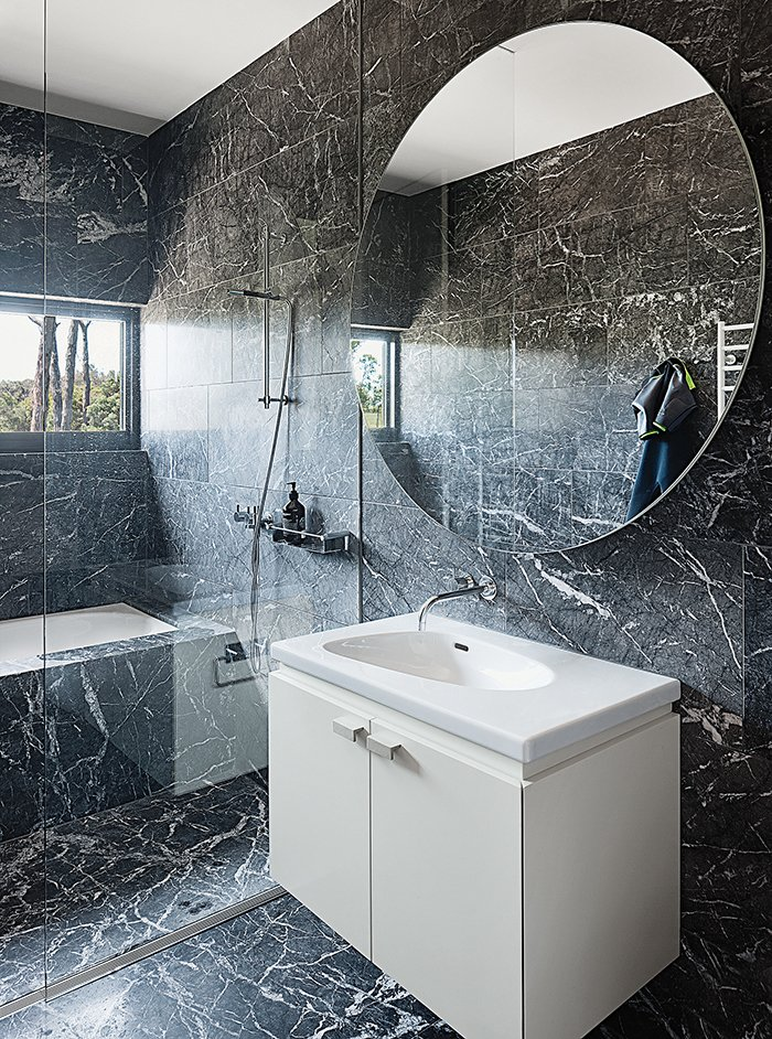 The marble continues in a bathroom, which has a Palomba sink from Laufen.  Photo 8 of 9 in A House That Looks as Natural as the Landscape