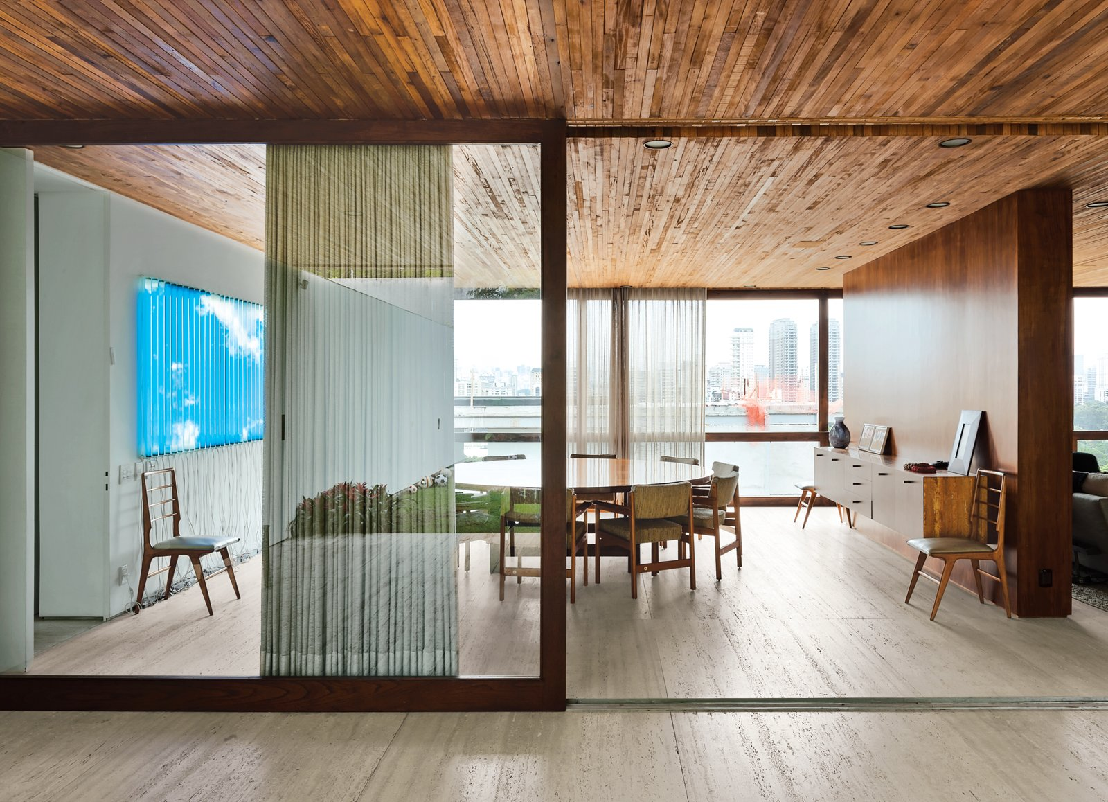 A wooden partition separates the dining room from the living room. The jacaranda table is a vintage find designed by Jorge Zalszupin for L'Atelier. The dining chairs are by the Brazilian designer Sergio Rodrigues and architect Isay Weinfeld designed the sideboard. The fluorescent lamp sculpture on the wall is Luz Natural by Eduardo Coimbra. Tagged: Dining Room, Chair, Table, and Light Hardwood Floor.  Photo 2 of 9 in Blockbuster Movies Can't Compete with These Monumental Views
