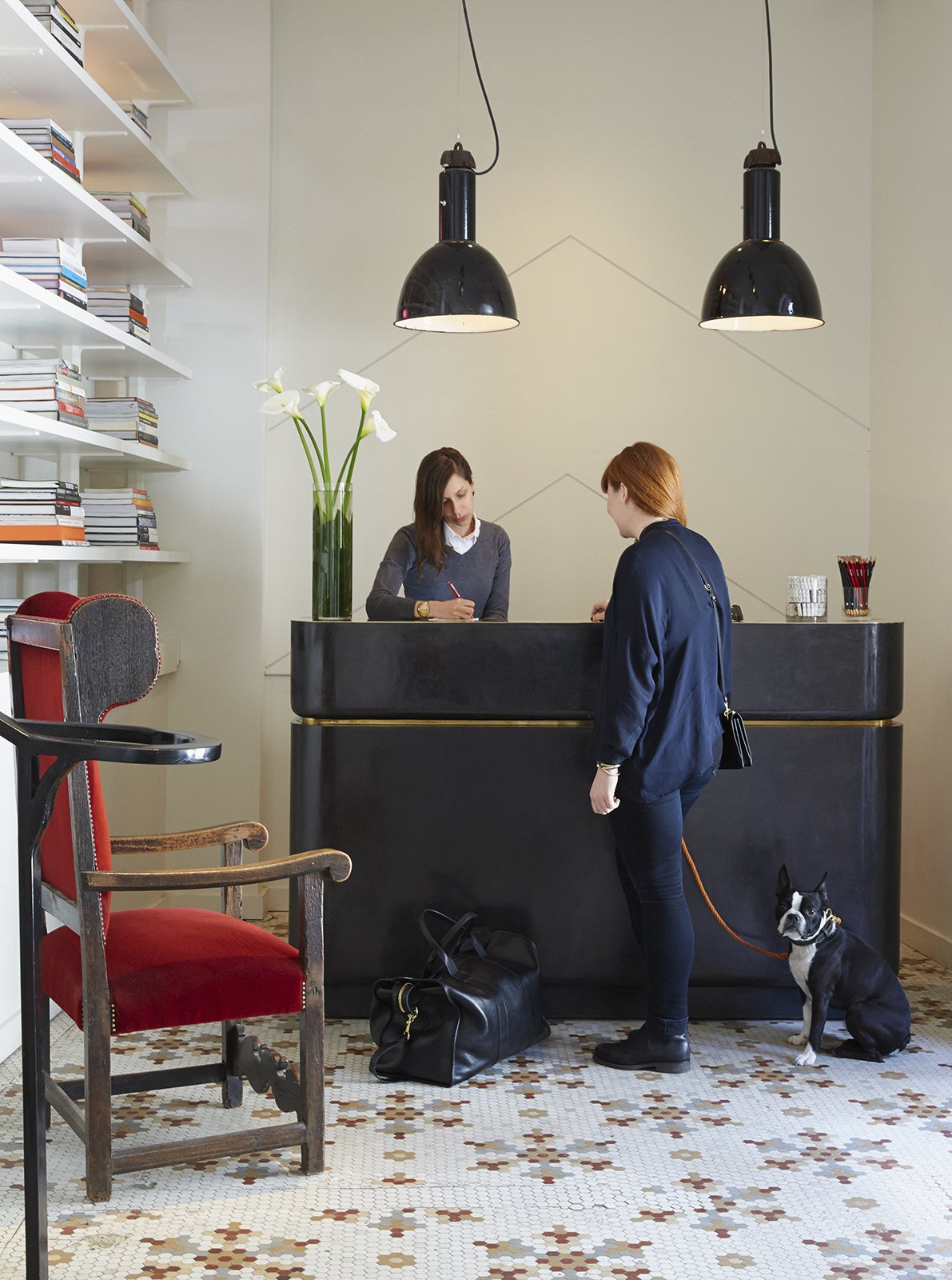 In the lobby, guests are greeted at a reception desk fabricated by NYC company FERRER and illuminated by vintage pendants sourced from Belgium. The ornate tile on the floor is original—a nod to the building's past.  Dogs Who Love Modern Design by Brian Karo from This Boutique Hotel Loves its City Like No Other