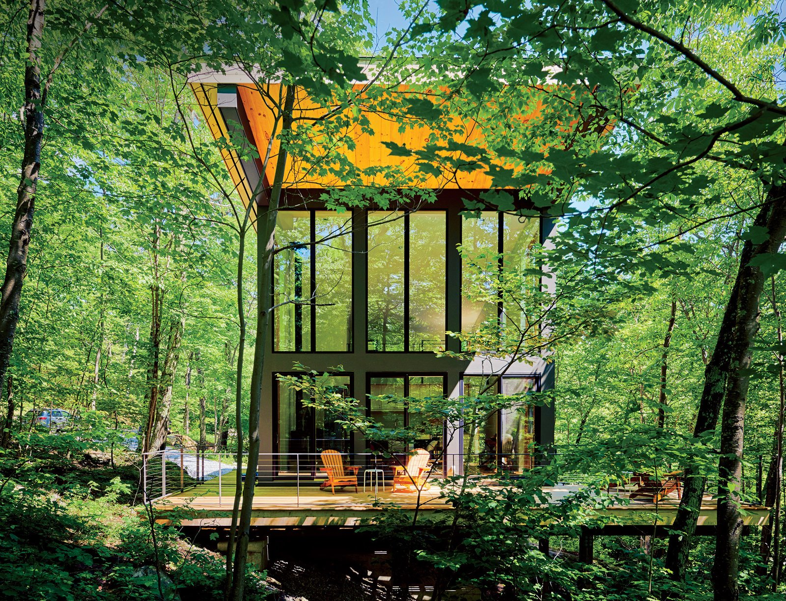 "A cantilevered cabin designed by R D Gentzler blends into the forest, even as it hovers above a 20-foot drop-off. Its south face is almost entirely glass, but a roof canopy limits solar gain. ""We sit on the deck all afternoon watching the trees, and the time just flies by,"" says resident Maricela Salas. Tagged: Exterior and House.  Modern, Off-the-Grid Homes by Aileen Kwun from A Little Cabin Reaches Such Great Heights"