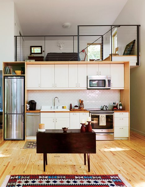 The kitchen and lofted guest bedroom take cues from urban living—including an apartment-size Summit refrigerator. The cabinets are IKEA and the tile is by Heath Ceramics.