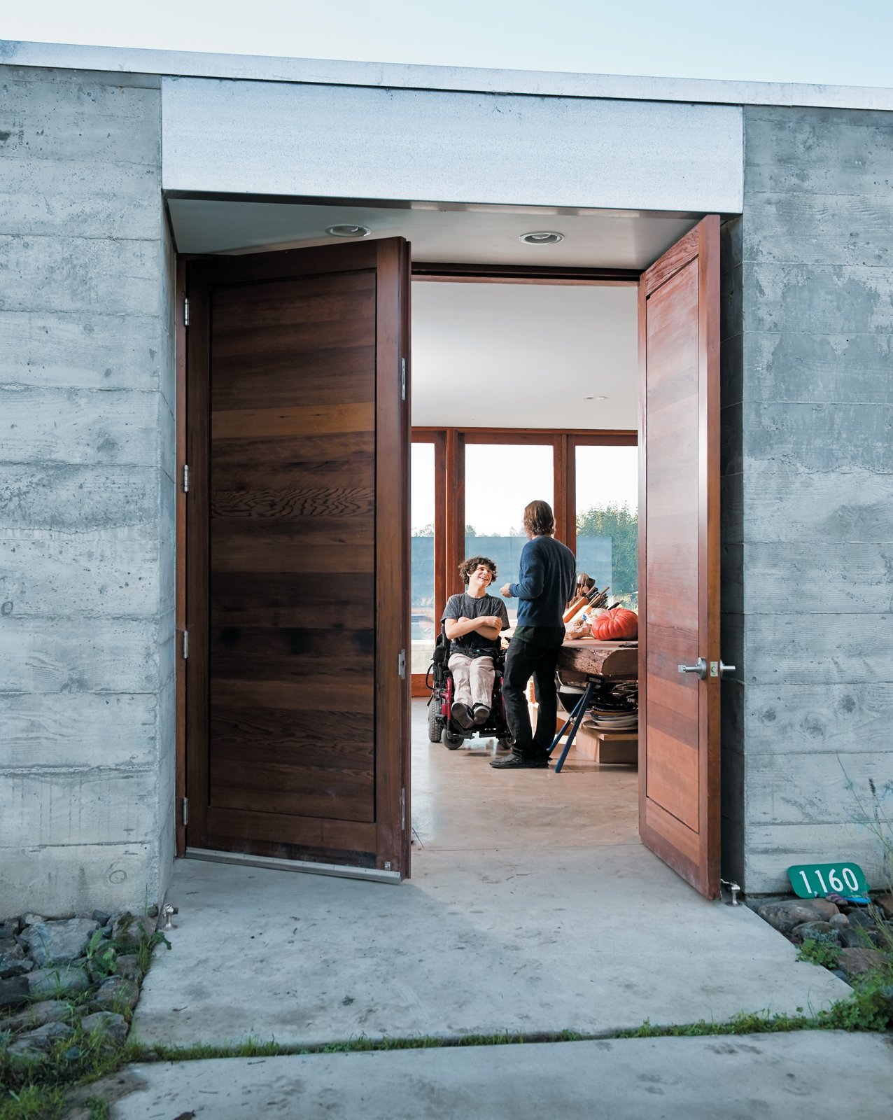 The wide front door opens onto a wide central living space where the entire family—and a regular cast of visitors—spends much of their time. Tagged: Doors, Exterior, Swing Door Type, and Wood.  Photo 3 of 18 in A Sonoma Prefab That Celebrates a Family's Passion for Cooking