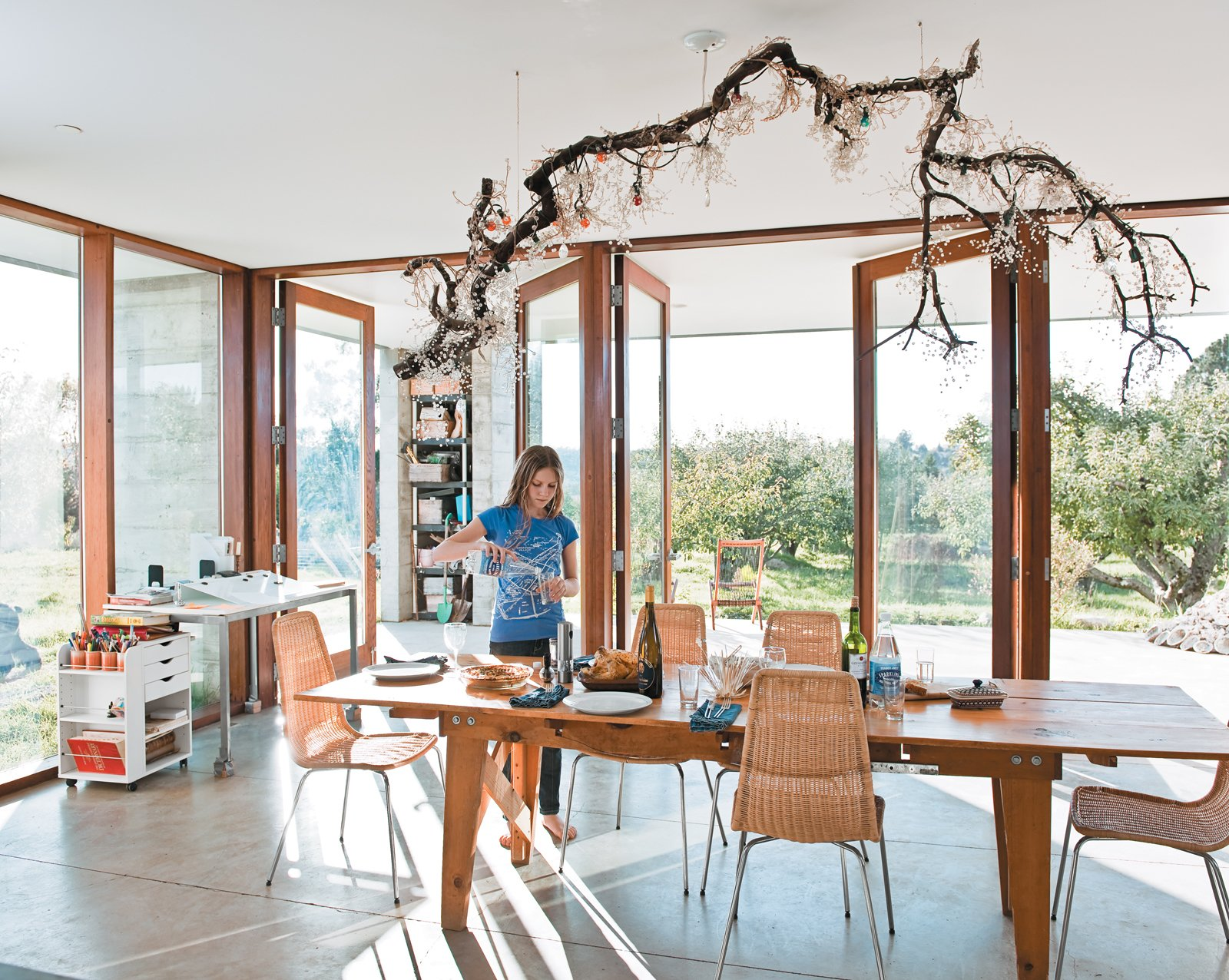 The dining room table sits at one end of the main room, with an open view onto the rows of trees that extend out from two sides of the house. Natasha sets the table underneath a suspended fixture made by her mother, Naomi, out of a salvaged branch, crystal pieces, and strung bulbs. A Sonoma Prefab That Celebrates a Family's Passion for Cooking - Photo 4 of 18