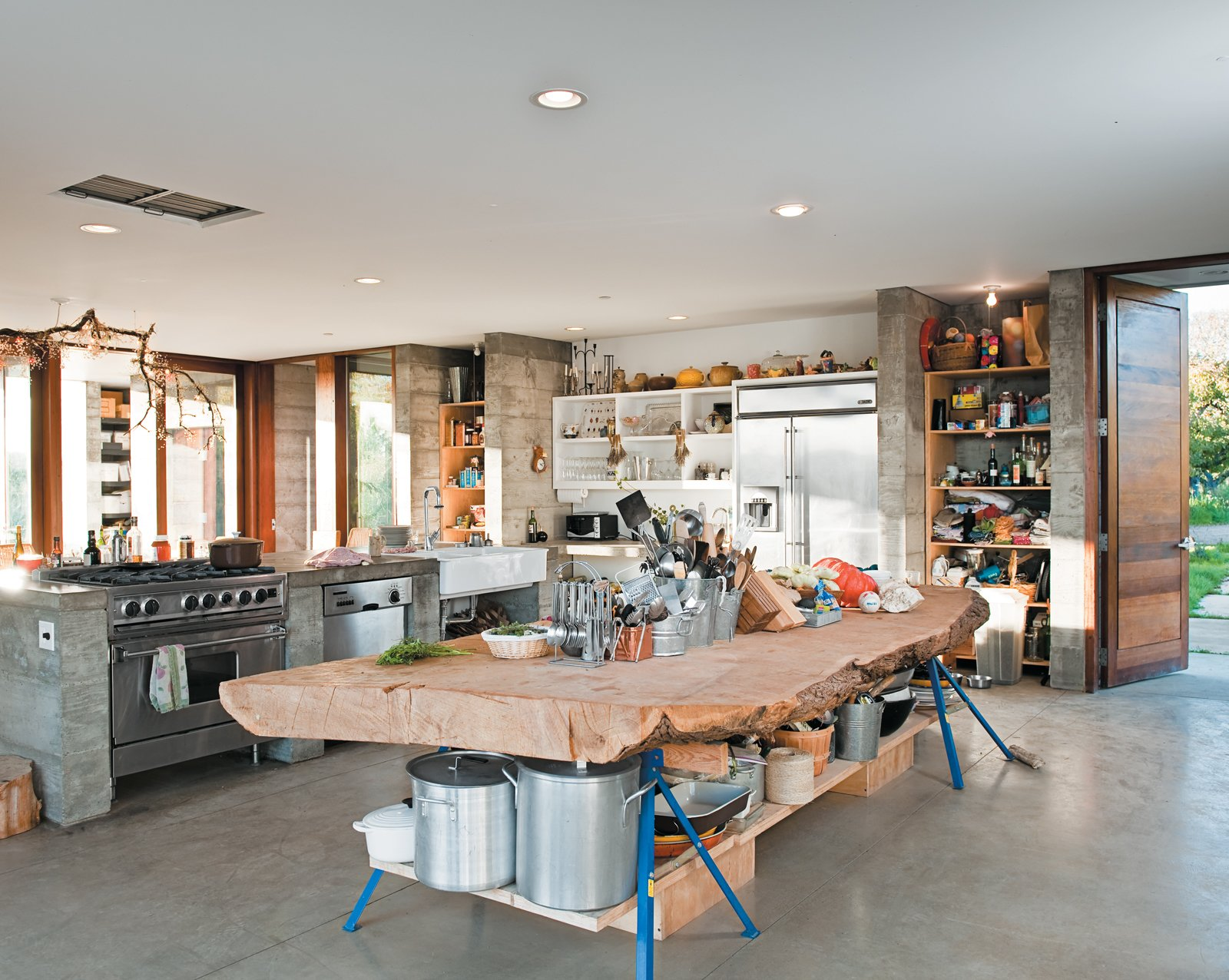 A massive slab of cypress perched atop sawhorses provides storage for pots and utensils. Tagged: Kitchen and Wood Counter.  Photo 5 of 18 in A Sonoma Prefab That Celebrates a Family's Passion for Cooking
