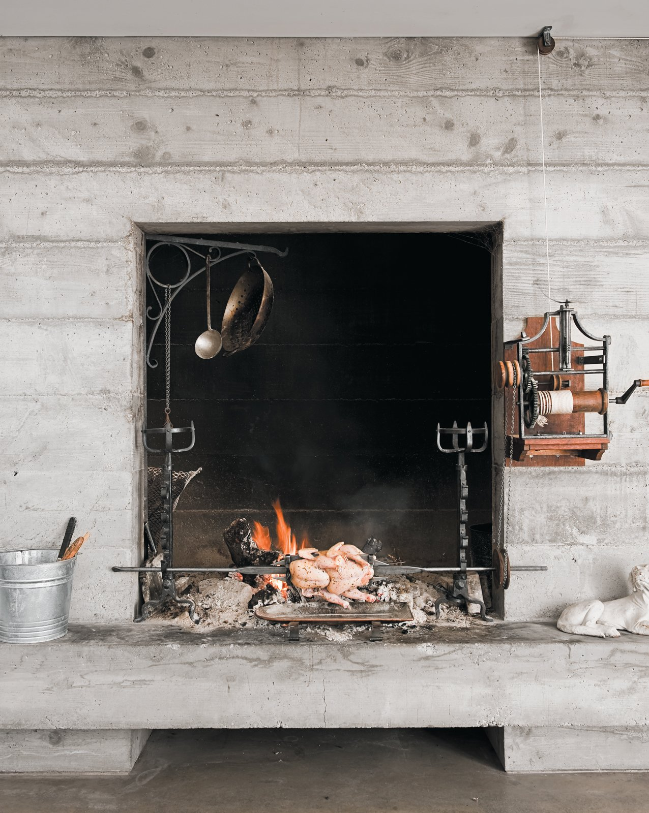 In the living room fireplace, a bird turns on the antique French spit.  Photo 11 of 18 in A Sonoma Prefab That Celebrates a Family's Passion for Cooking