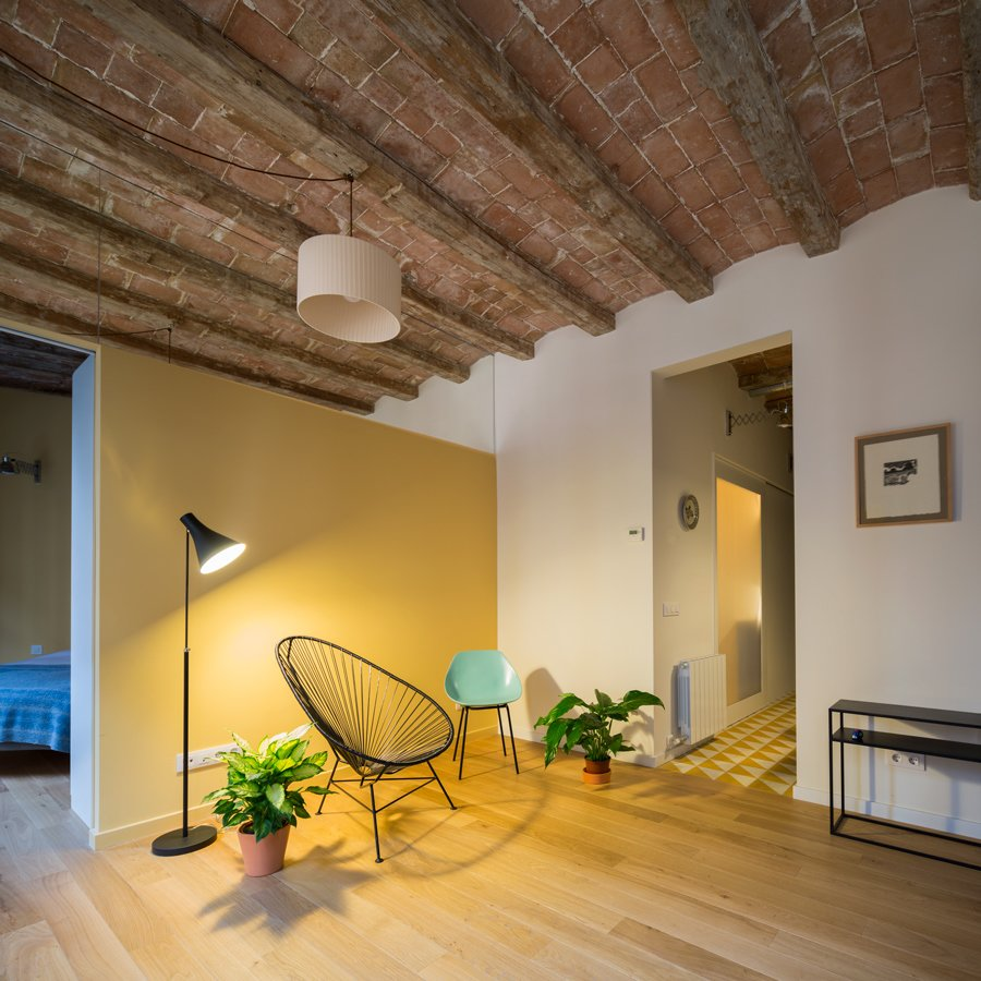 The partition separating the bedroom from the living room appears to be a partial wall—but in reality, a mirror extends from the top of the wall to the ceiling.  Photo 5 of 6 in In Barcelona, Vaulted Ceilings Are Always a Win