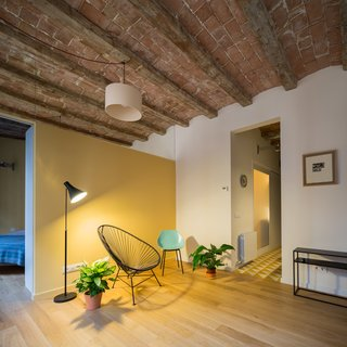In Barcelona, Vaulted Ceilings Are Always a Win - Photo 4 of 5 - The partition separating the bedroom from the living room appears to be a partial wall—but in reality, a mirror extends from the top of the wall to the ceiling.