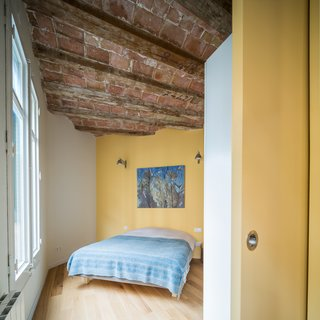 In Barcelona, Vaulted Ceilings Are Always a Win - Photo 5 of 5 - The apartment, approximately 765 square feet in total, contains one master bedroom as well as a smaller sleeping space for guests. A sliding door closes off the bedroom from the living area when total privacy is desired.