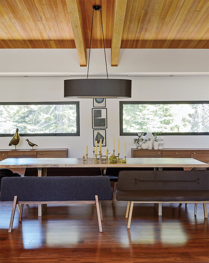 An oversize oval black linen shade from Dogfork Lamp Arts hangs above a table Maca created out of a wood slab from West Marin-based artisan Evan Shively of Arborica. The bench seats are De La Espada; the brass candelabrum is vintage, sourced from 1stDibs. The credenzas are Bo Concept. Tagged: Dining Room, Pendant Lighting, Table, Storage, Medium Hardwood Floor, and Bench.  Photo 4 of 11 in The Ski Retreat for All Seasons