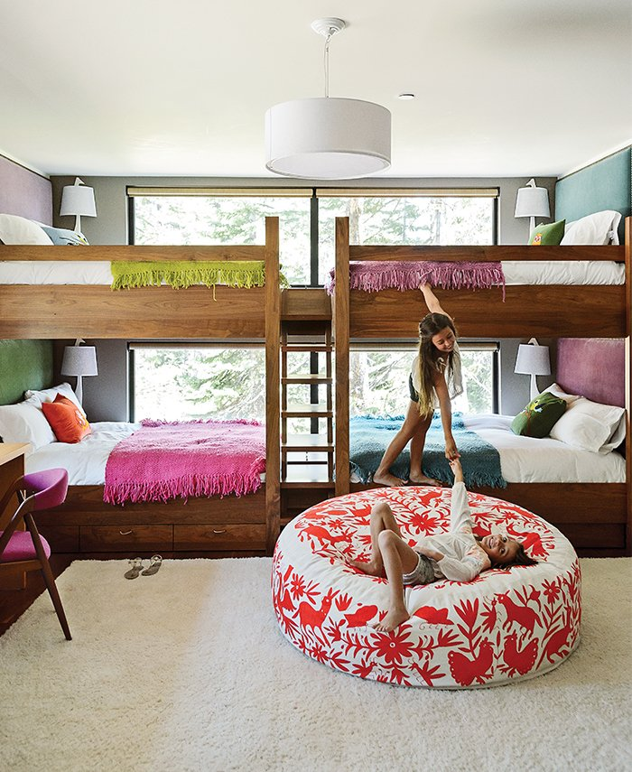 In the kids' bunk room, Maca designed walnut beds with built-in storage and fabric headboards, and covered each one in hand-knit blankets by Marcela Rodriguez-Chile. The giraffe sconces are from Jonathan Adler. The girls play on a hand-embroidered Olli lounger from Heath Ceramics. Tagged: Kids Room, Bunks, Bedroom, and Rug Floor.  Photo 6 of 11 in The Ski Retreat for All Seasons
