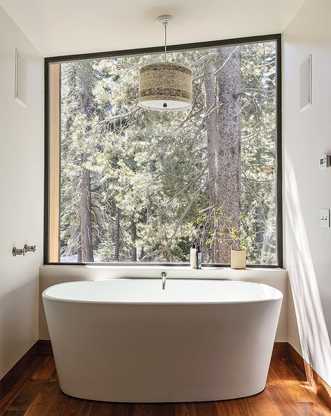In the master bathroom, a matte Ove tub from Wetstyle is one of Maca's favorite getaways. The angle of the custom window, designed with a minimal frame to maximize the view, mimics the roofline.