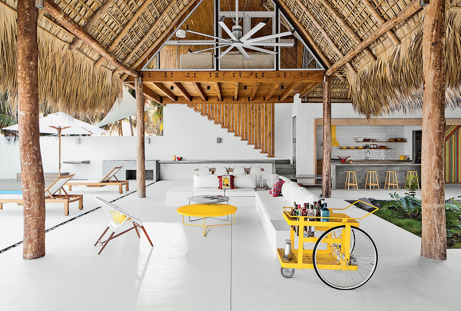 The living-dining area of a beach house designed by El Salvador firm Cincopatasalgato features a custom bar cart by local designers Claudia & Harry Washington, a built-in sofa, and an Ikono chair and Circa low tables by The Carrot Concept. Bursts of Yellow and Indoor Gardens Are Just Two Reasons to Love This Home - Photo 2 of 6