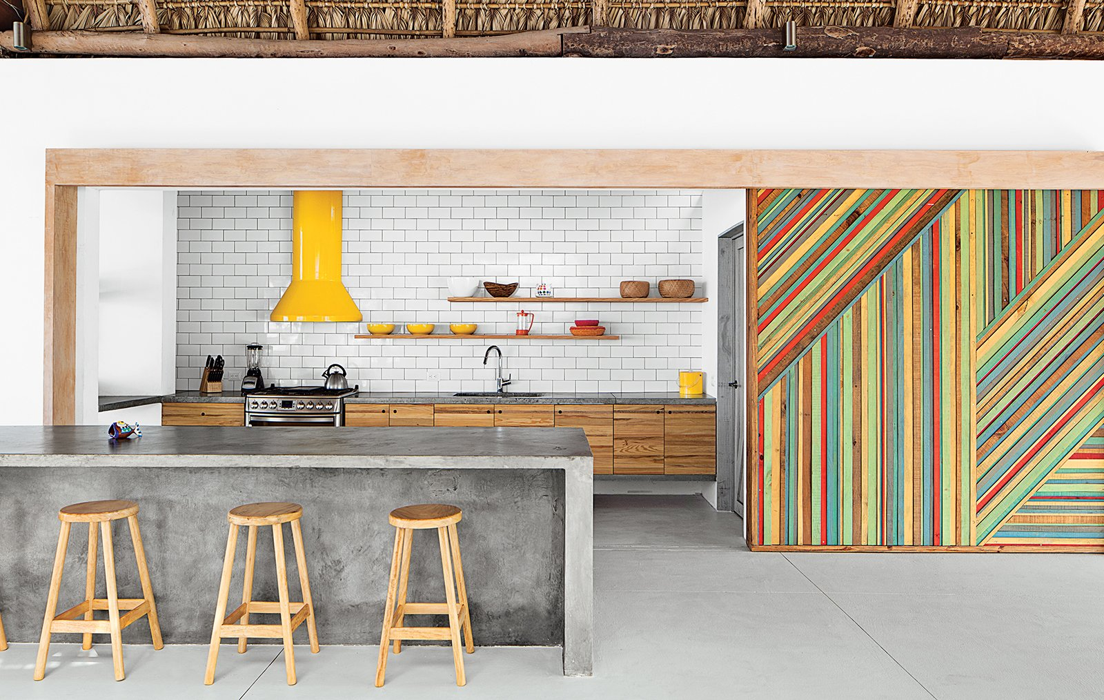 By eliminating walls and incorporating a series of interior gardens, architect José Roberto Paredes creates an eclectic and inspired El Salvador beach house. In the kitchen, rough-hewn materials like a eucalyptus-log-and-thatch roof offset the monolithic concrete island and glossy subway tile backsplash. Claudia & Harry Washington built the vivid wooden sliding walls, which are inspired by the palm leaves that change color and create diagonal patterns in trees near the house. The bar stools were a street market discovery. Bursts of Yellow and Indoor Gardens Are Just Two Reasons to Love This Home - Photo 3 of 6