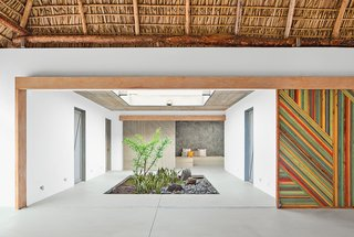 "Bursts of Yellow and Indoor Gardens Are Just Two Reasons to Love This Home - Photo 3 of 5 - Architect José Roberto Paredes calls the sliding walls utilitarian artwork. ""The doors open to a surprise space, like a secret pathway,"" he says."