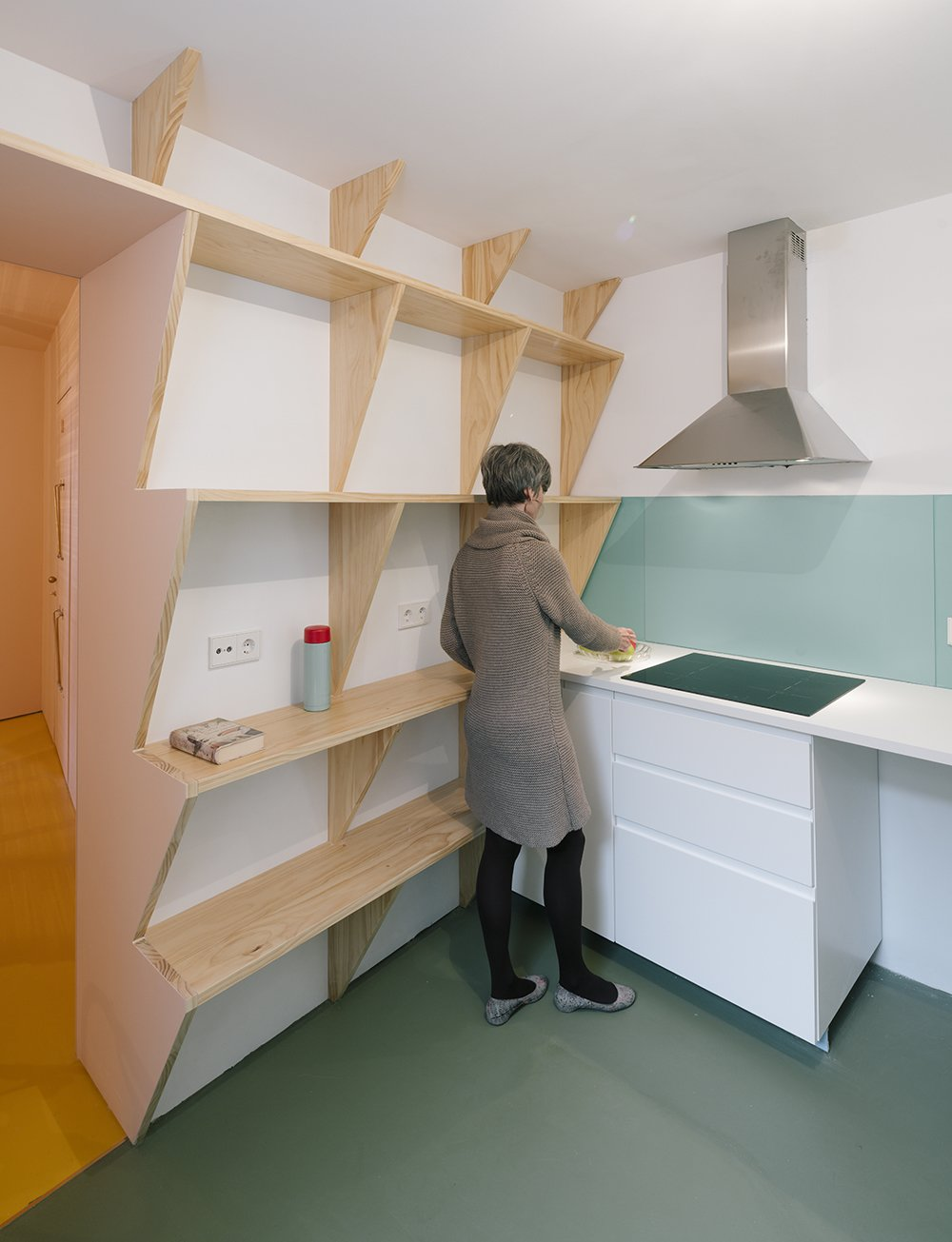 At just under 1,400 square feet, the three-bedroom apartment benefits from built-in space savers including sawtooth shelving and even a fold-out bench. Tagged: Kitchen, White Cabinet, and Range Hood.  Photo 5 of 7 in A Quirky Renovation Brings an Indoor Garden to the Center of Madrid